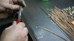Hands of worker with tools and wire, cut off the pieces fall to table Stock Footage