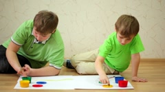 Two boys sit and draw ink on paper using their fingers Stock Footage