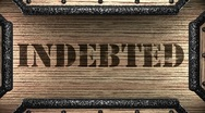 Indebted on wooden stamp Stock Footage