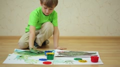 Boy draws color paints with his palm and fingers on sheet Stock Footage