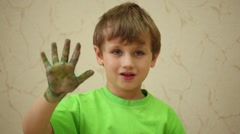 Boy waves his right palm smeared with coloured paints Stock Footage