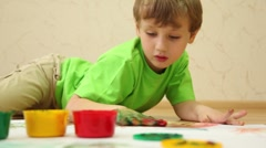 Boy lay on floor and draws color paints with his palm Stock Footage