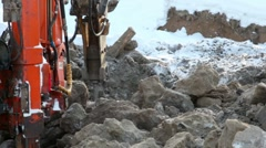Machine boring terrestrial rocks in winter, pile of ground beside it Stock Footage