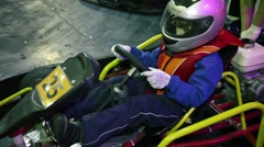 Little boy in helmet and racer suit sits in cart, coach crank an engine Stock Footage