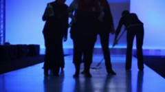 Several people cleaning podium in dark after show Stock Footage