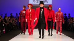 Men wear red suits and top hats from Slava Zaytzev walk the catwalk Stock Footage