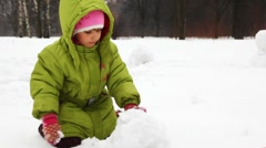 Girl play with snow and make snowman Stock Footage