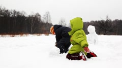 Little children play with snow and make snowman Stock Footage