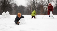 Mother with two children make snowman in winter Stock Footage