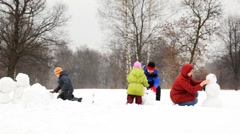 Mother and father with two children make snowman, part3 Stock Footage
