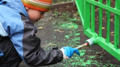 Little boy with paintbrush in hand carefully dye fence on community work day Stock Footage