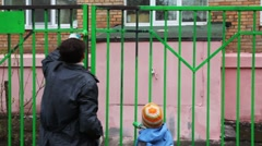 boy and father with paintbrush in hand carefully dye fence on community work day - stock footage