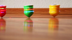 Toy tops with bright lights roll on table upside down Stock Footage