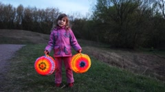 Little girl hold and raise two balls from paper at night Stock Footage