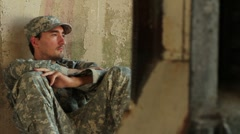 Distraught soldier sitting against concrete wall - stock footage