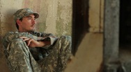 Stock Video Footage of Distraught soldier sitting against concrete wall
