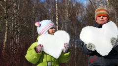 Little boy and girl hold heart made of snow in winter Stock Footage