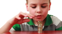 boy takes off coins placed column and puts it on red base - stock footage