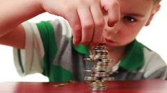 Boy makes highly complicated figure with coins on red base Stock Footage