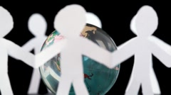 Paper people stand holding hands and rotates around transparent globe Stock Footage
