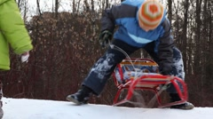 Boy with sled ride down mountain, and then girl behind him Stock Footage