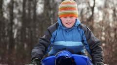 Boy on sled pushes his hands and ride down snow mountain Stock Footage