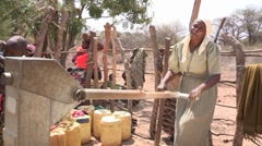 Happy Woman Pumps at the Borehole Stock Footage