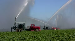 Irrigation trucks water fields. - stock footage