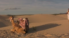Camel and middle east people in the desert sand dunes - stock footage