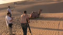 Film crew in the desert sand dunes with a camel - stock footage