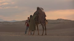Middle east guy gets off a camel in the sahara desert - stock footage