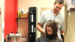 Hairdresser drying a student's hair - stock footage