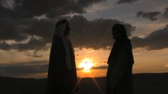 Two middle eastern people talking in the sunset of the sand dunes Stock Footage
