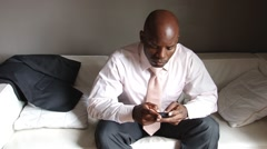 Frustrated black businessman with cell phone sending text - stock footage