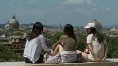 Three girls sat on wall looking at Roman view Stock Footage