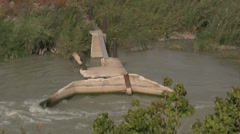 Water from a canal by a dam with a wood bridge Stock Footage