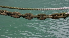 Old rope and chain over the water - stock footage