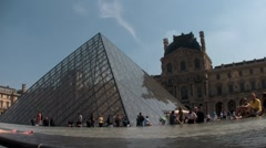 Crowds of people walk around the grounds of Louvre in Paris. Stock Footage