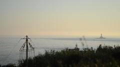 Afternoon at the ocean and distant lighthouse Stock Footage