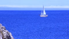 Sailboat sailing across sapphire blue water (HD) k Stock Footage