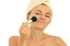 Young attractive woman applying blusher, isolated on white Stock Footage