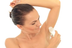 Young attractive woman using an antiperspirant, isolated on white Stock Footage