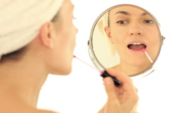 Woman applying pink lipstick in the mirror, isolated NTSC Stock Footage
