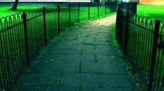 Walking narrow stone path with fence a grass point of view Stock Footage