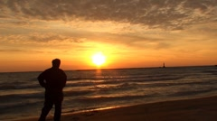 Man watch sunrise from the beach Stock Footage