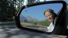 Girls reflection in a rearview mirror, moving car. Stock Footage