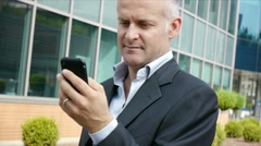 Man smiling near office building with mobile phone Stock Footage