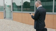 Man walking near office building and talking on cell phone Stock Footage