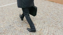 Businessman walking to work with suitcase. Closeup of legs and feet - stock footage