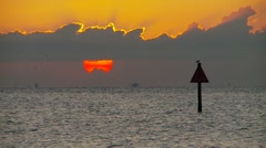 Sunset thru clouds (Channel marker in foreground) - stock footage